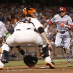 Billy Hamilton  is tagged out at home by San Francisco Giants catcher Buster Posey (28) during the sixth inning of Thursday's game at AT&T Park.
