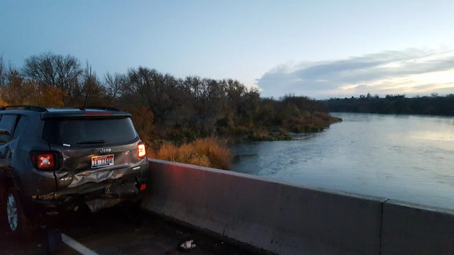 In this photo provided by Oregon State Police, a damaged car is shown on an Interstate 84 bridge over the Snake River on the Idaho/Oregon border near Ontario, Ore., Monday, Nov. 21, 2016. An Idaho man not only survived being hit by a car on an icy interstate highway bridge but also a 50-foot-fall into a river and a swim through its frigid waters with a badly broken leg, authorities said.