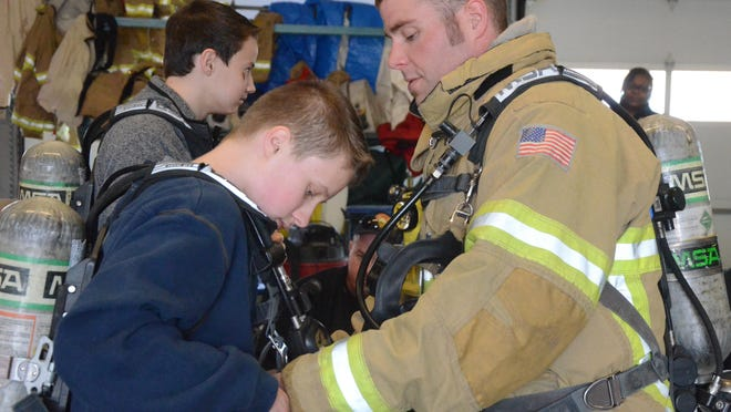 Battle Creek firefighter Shea Peters shows Carl Dull, 16, of Pennfield High School how to put on an air tank.