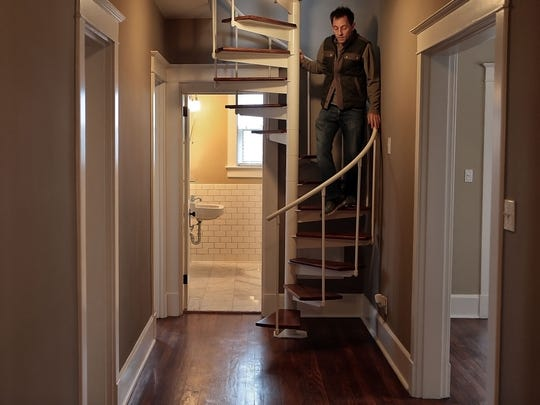Tobey Hubbard walks down from the master bedroom suite in a condo for sale at The Greenstone, a 91-year-old development which is listed on the National Register of Historic Places.
