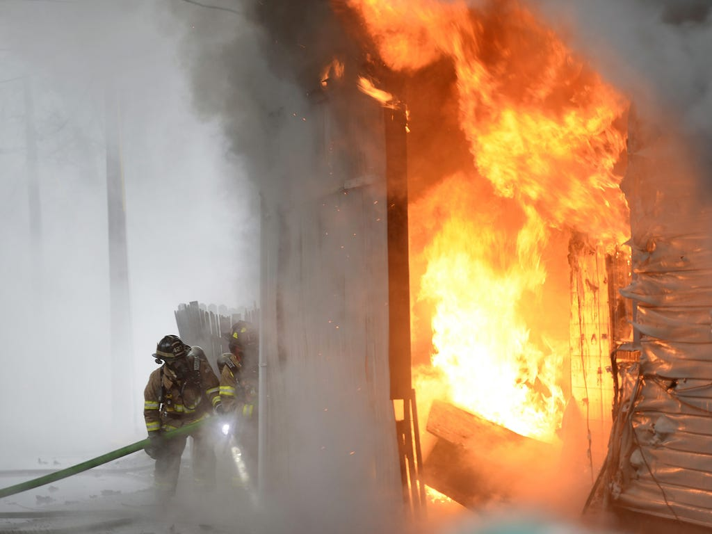 Lebanon City firefighters battle a three-alarm blaze at 519 North 11th Street on Dec. 2 in Lebanon, Pa. The three hour fire damaged three homes and left nine people homeless.