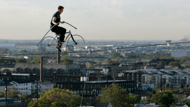 Nik Wallenda pedals a bicycle on a wire 12 stories above the street in Newark, N.J., on Oct. 15, 2008.