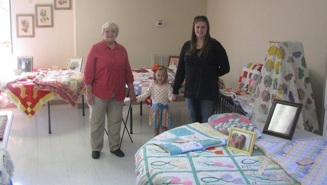 A longstanding Stewart County resident who is also a Senior Citizen Center member, Nelda Saunders, left, stands amid six generations of family quilts, from her grandmother's quilts to those belonging to her great-granddaughter. All were lovingly crafted by family members over the years. She is pictured with her breat-grandaughter, Allie Marie Saunders, center, and granddaughter Ashley Saunders, right.