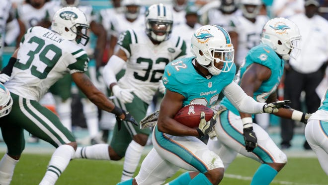 Miami Dolphins running back Kenyan Drake (32) runs for a touchdown during the second half of an NFL football game against the New York Jets, Sunday, Nov. 6, 2016, in Miami Gardens, Fla. The Dolphins defeated the Jets 27-23.