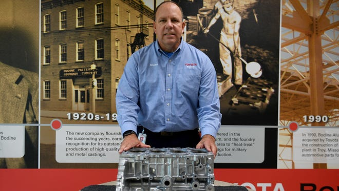 Shawn Daly General and Plant Manager of Toyota Bodine Aluminum in Jackson stands behind the Toyota New Global Architecture 2.5L engine block that is currently in production.
