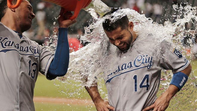 Kansas City Royals' Salvador Perez pours water onto Omar Infante after the Royals defeated the Cleveland Indians 8-4 in a baseball game, Thursday, Sept. 17, 2015, in Cleveland.