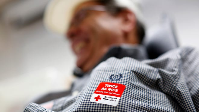 """Ken Van Wychen wears a sticker in honor of being a double red cell donor during a blood drive at the National Guard Armory in Green Bay, Wis., on Monday, July 28, 2014. The American Red Cross has an """"urgent"""" need for blood donations this summer."""