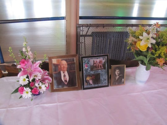 Flowers and photographs of the late Thomas Sloniger remain on a table at Joycrest Skating Rink the day after an April 16 memorial skate in his honor, where $1,000 was raised in his name for the Arctic League and Holy Family Catholic Schools.