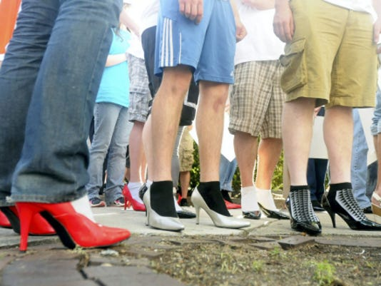 Men walk in high-heel shoes during the Walk a Mile in Her Shoes sponsored by Women In Need in 2013.