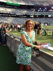 "In this photo taken Aug. 7, 2014, Connie Carberg, who served as a scout for the New York Jets from 1976 to 1980, poses near the sideline at MetLife Stadium in East Rutherford, N.J. Carberg, the first woman to work as a scout for an NFL team, says the Buffalo Bills' hiring of Kathryn Smith as the league's first full-time female assistant coach is a ""great opportunity"" for women. (Elisabeth Meinecke via AP) NO SALES"