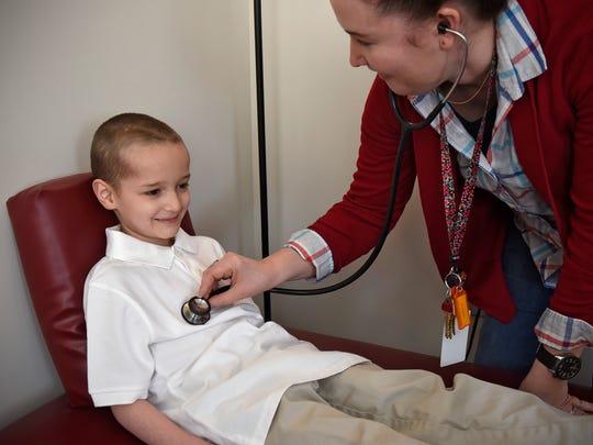 STRIDE Academy nurse Kelly Meyer checks on student Vincent Westlund at the school Friday, Feb. 12, 2016.