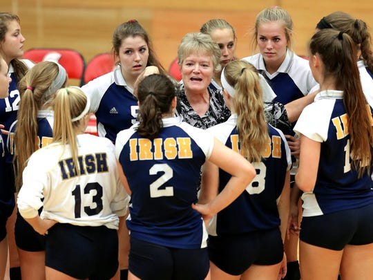 Cathedral head coach Jean Kesterson talks with her players during their match against Center Grove held at Center Grove High School on Tuesday, August 25, 2015. Cathedral pulled off the win in the 5th set.