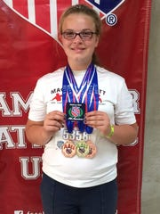 Valadian Pallett proudly displays the AAU medals and