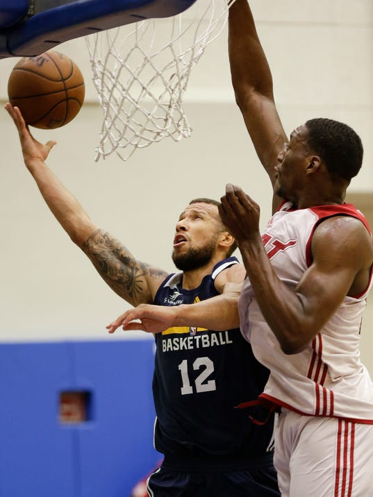 FILE - In this Monday, July 3, 2017 file photo, Indiana Pacers' Trey McKinney-Jones (12) takes a shot against Miami Heat's Bam Adebayo during the first half of an NBA summer league basketball game  in Orlando, Fla. There's a handful of players who are getting to play for two NBA teams this summer, a grind which they hope pays off down the road. Trey McKinney Jones, Dylan Ennis and Naz Mitrou-Long are among those who played for one team in Orlando and Salt Lake City, and will switch jerseys once they get to the NBA's biggest summer league in Las Vegas. (AP Photo/John Raoux, File)