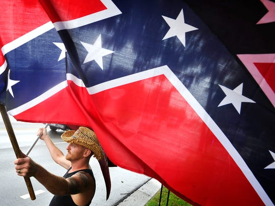 Veteran Rick Martin, waves the Confederate Battle Flag