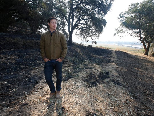Adam Mariani poses in a burned area of the Scribe Winery