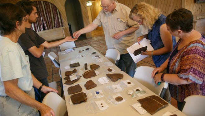 Robert Schuyler, a professor of archaeology from the University of Pennsylvania, shows visitors some of the artifacts that have been uncovered at the ghost town during an archaeology workshop in the Cosmopolitan Restaurant Friday, May 13, 2016.