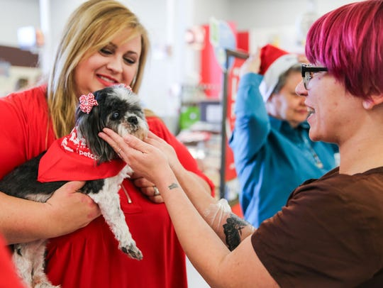 Maddy Day, salon leader, greets Jenie Wilson and Tzuki before Wilson receives a grant for Concho Valley PAWS on Dec. 13 at Petco.