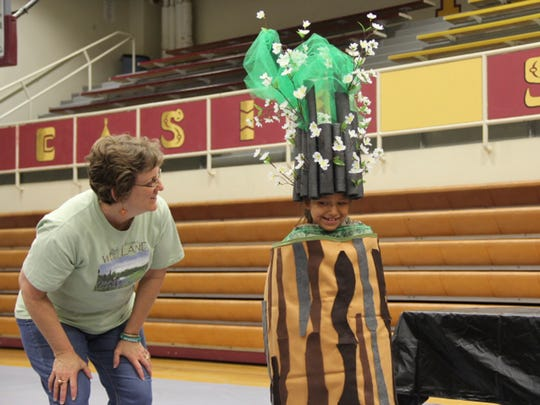 Cat Lynch, formerly the director of education at ZooMontana in Billings, illustrates the growth of trees by wrapping Ashlynn Bullchief, a Poplar first-grader, in simulated tree layers, topped with a crown of foliage.