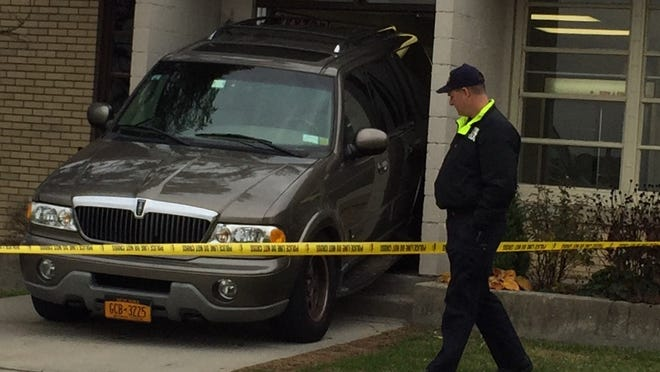 A Lincoln Navigator rammed into a door at a Westchester County Airport building, injuring a person on the other side of the door, Nov. 13, 2014.