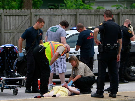 A man in handcuffs is tended to by paramedics after being hit by a police car at National Avenue and Edgewood Street on Wednesday, June 11, 2014. The man stabbed at a sheriffs deputy as they were attempting to arrest him and fled on foot when he was struck by a police car a block away.