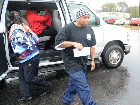 Former inmate Corey Garrett takes his paycheck to be
