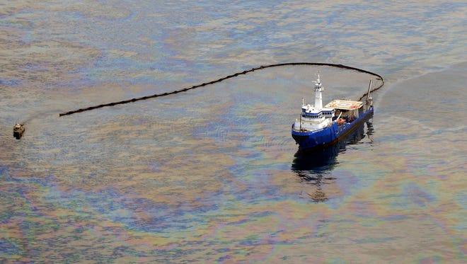 A boat conducts skimming operations as oil floats in the Gulf of Mexico, spilled from the collapsed Deepwater Horizon on June 13, 2010.