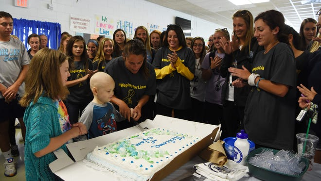 "Kristen Perry, center, a physical education teacher and the field hockey coach at John Jay High School, cuts the cake for Liam Craane, 5, center left, who is battling pediatric cancer. Through the Friends of Jaclyn Foundation, Liam was ""adopted"" by the school's field hockey team."