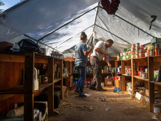 Cindy Lanouette and Rev. Steve Brigham clean up the food storage shed as they work to break down much of the tents not needed for everyday living as they prepare the homeless camp for closing.