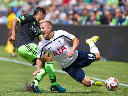 Tottenham Hotspur's Lewis Holtby (14) is tackled by Seattle Sounders' DeAndre Yedlin during the first half of a friendly soccer match in Seattle, Saturday, July 19, 2014. (AP Photo/Stephen Brashear)