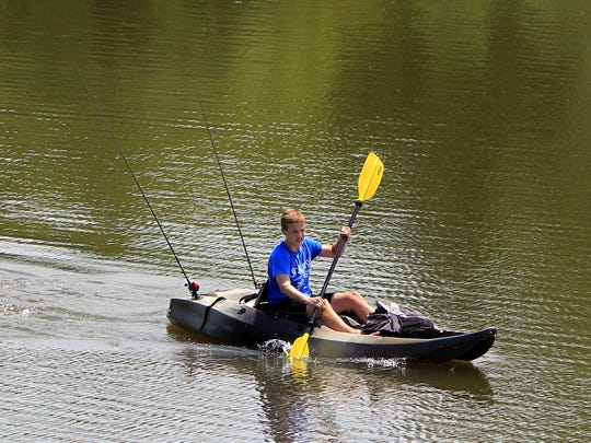 A kayaker paddles across the lake at Winton Woods Park. If a levy is approved by voters this fall the park district wants to make upgrades to playground equipment at Winton.