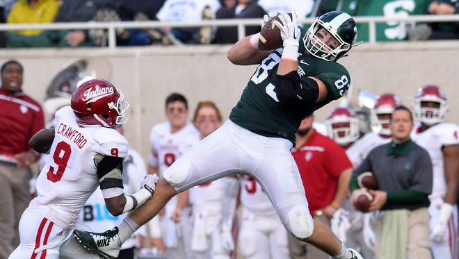 MSU tight end Paul Lang leaps for a first down catch   against Indiana's Jonathan Crawford Saturday 10/24/2015.