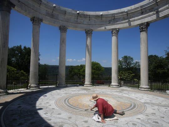 Artist Haifa Bint Kadi repairs a mosaic in the Temple