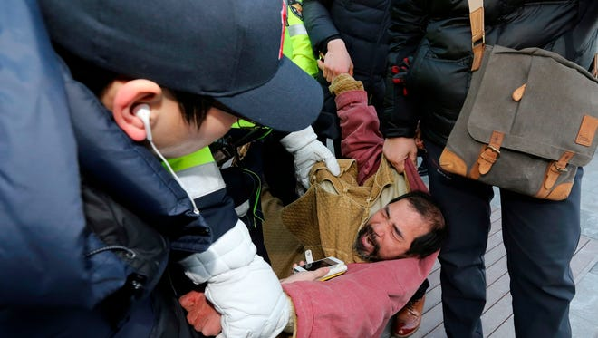 A suspect, center, identified by police as 55-year-old Kim Ki-jong, is detained by police officers in Seoul, South Korea, Thursday, March 5, 2015. U.S. Ambassador Mark Lippert was slashed on the face and wrist by a man wielding a knife with a 10-inch blade and screaming that the rival Koreas should be unified, South Korean police said Thursday.