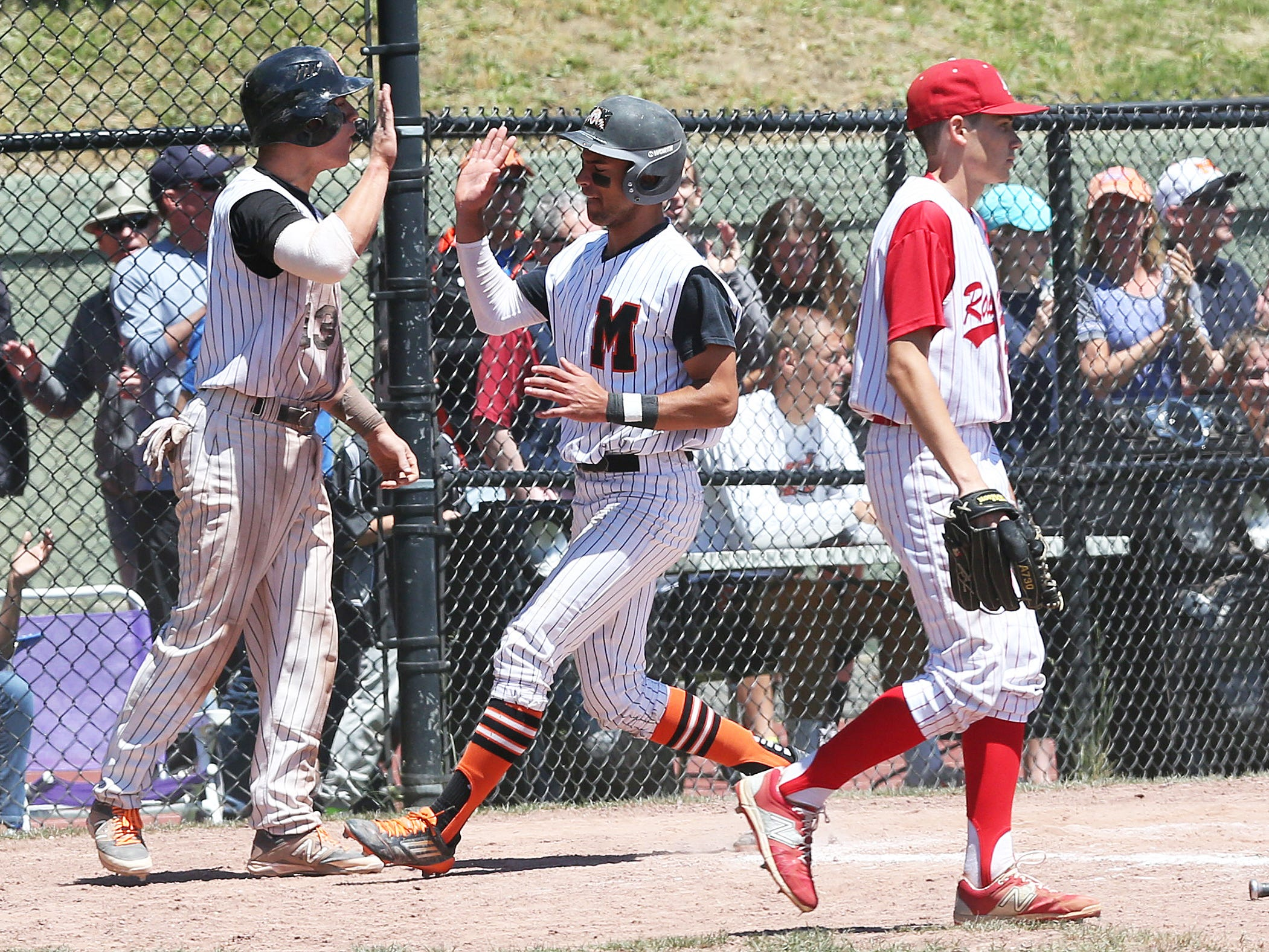 From left, Mamaroneck's Andy Karlan and Andrew Gross celebrate after scoring on Kumar Nambiar bases clearing double against North Rockland in a boys baseball playoff game at Mamaroneck High School on Saturday, May 23, 2015. Mamaroneck won the game 5-3.