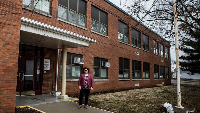 Jenifer Roberts, administrative director of the Thomas J. Evans Foundation, stands in front of the old Maholm Elementary and Par Excellence school on Maholm Street in Newark. The building will be remodeled and become the Boys and Girls Club of Newark. The foundation, established in 1965, supports recreational facilities and leases property to non-profit organizations.