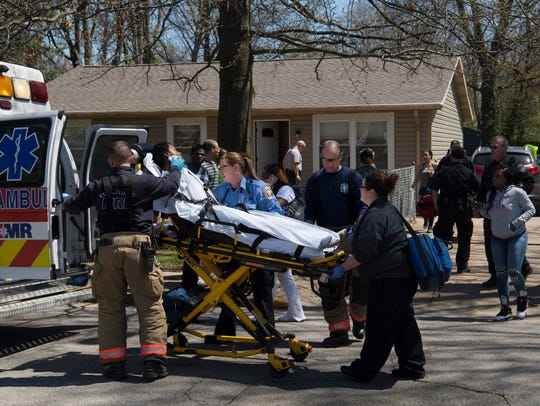 Emergency personnel use a stretcher to transport a