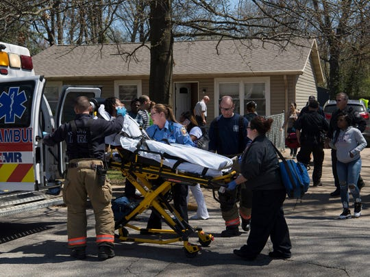 Emergency personnel use a stretcher to transport a shooting victim from a home at 926 Judson Street in Evansville to a local hospital Friday afternoon. Two subjects of interest were picked up by police near the intersection of Madison Avenue and Elliott Street a short time later. The wound to the right jaw of the victim didn't appear to be life-threatening.