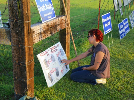 Gina Grimm, daughter of inmate Jack Jones, touches
