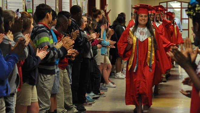 Graduating Pineville High School seniors led by Anna White walk through the halls of J.I. Barron Sr. Elementary Schoolin cap and gown Monday.