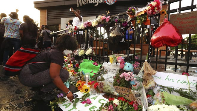 Tayla Myree sets out flowers on a shrine at a burned Wendy's on Sunday, June 14, 2020, in Atlanta. Rayshard Brooks, a 27-year-old Black man, was fatally shot by a white Atlanta police officer outside the Wendy's on Friday night.