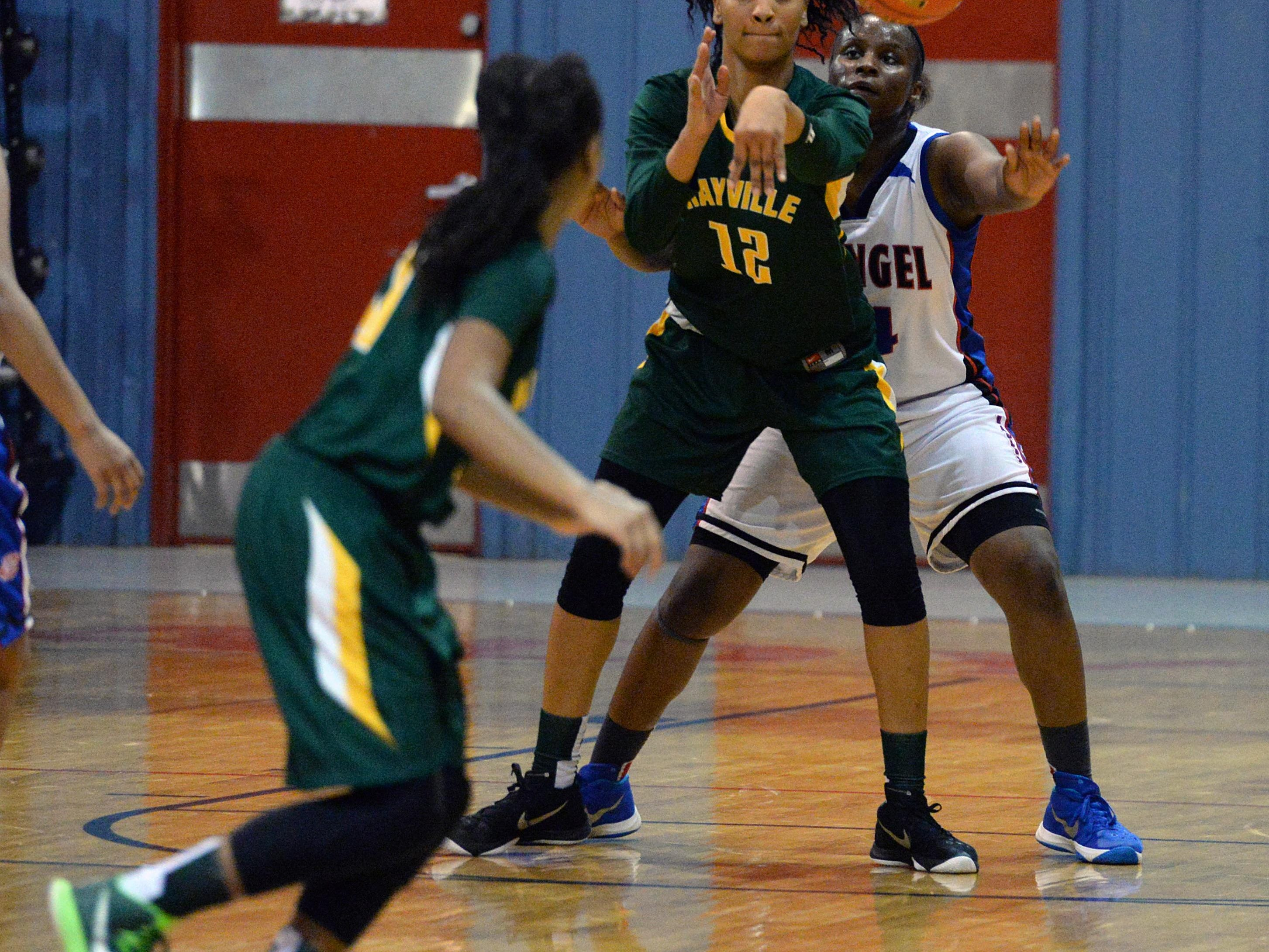 Micaela Wilson of Rayville passes the ball to a teammate as Evangel's Breanna Frierson looks on.