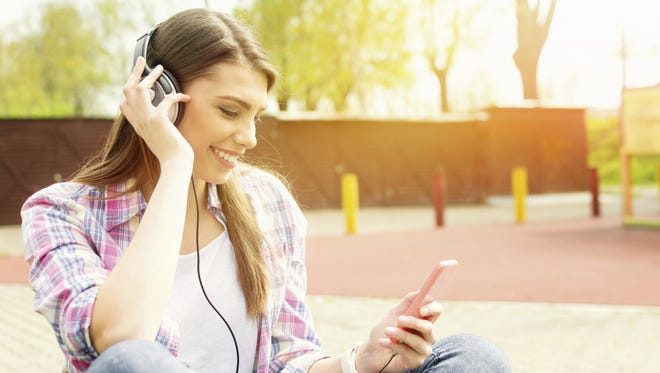 Young woman with headphones in park listening to music