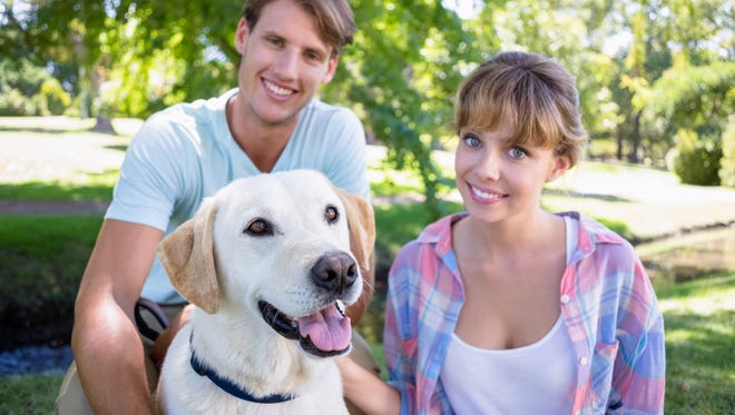 Couple with their labrador dog in the park.