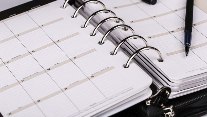 Personal organizer or planner with pen on white background.