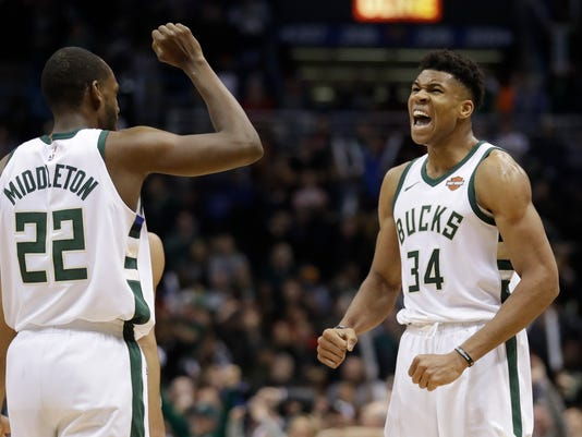 Milwaukee Bucks' Giannis Antetokounmpo celebrates with Khris Middleton (22) after making a basket and being fouled during the second half of an NBA basketball game against the Cleveland Cavaliers Tuesday, Dec. 19, 2017, in Milwaukee. The Bucks won 119-116. (AP Photo/Morry Gash)