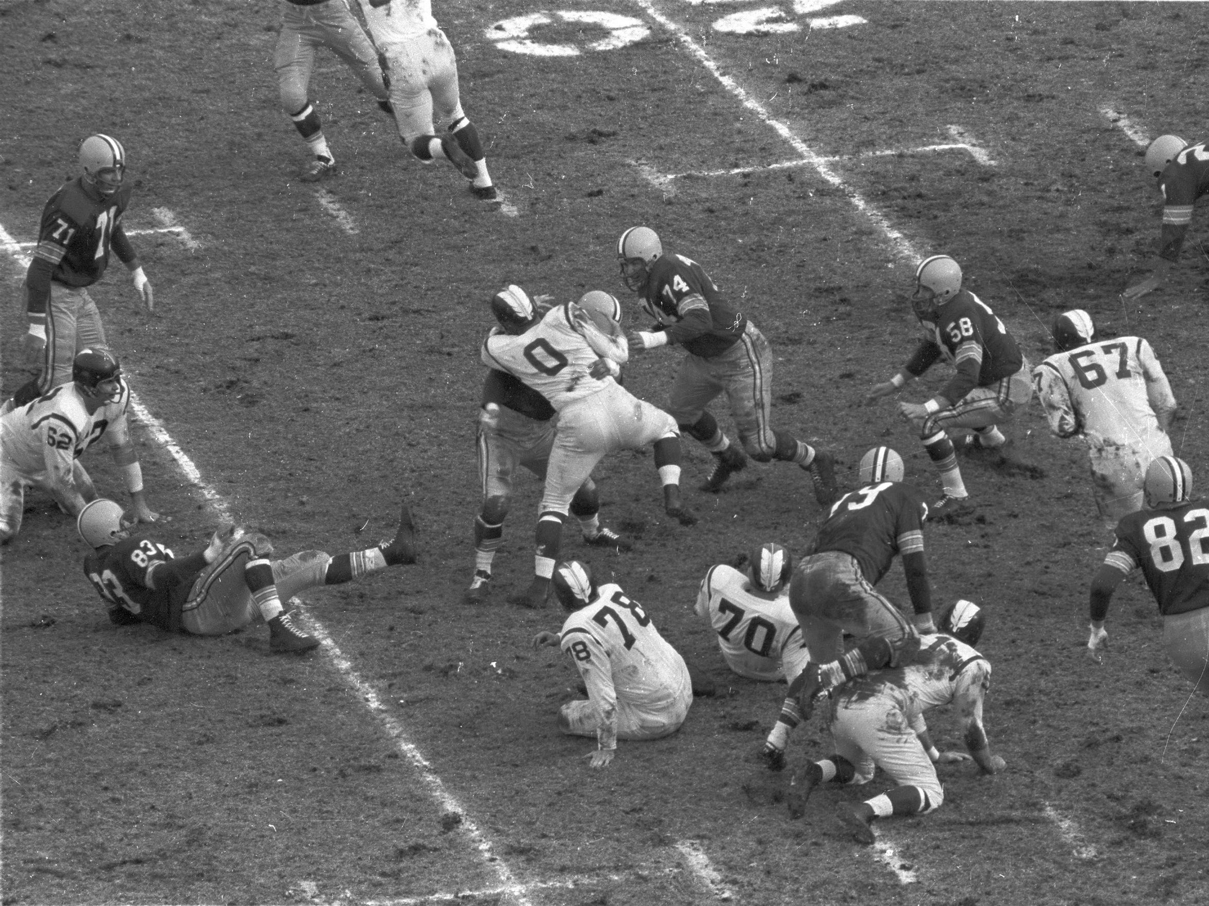 Washington running back Johnny Olszewski (0) is wrapped up by one Green Bay defender and surrounded by a host of others, including defensive tackle Henry Jordan (74), in the Packers' 21-0 victory at new City Stadium on Nov. 23, 1959. Clockwise from lower left, the Packers are defensive end Bill Quinlan (83), linebacker Bill Forester (71), defensive tackle Henry Jordan (74), linebacker Dan Currie (58), defensive end Jim Temp (82) and defensive tackle Dave Hanner (79). The Washington linemen are, from left, Don Boll (62), Don Lawrence (78), Jim Schrader (51) and Ray Lemek (70) on the ground and Don Stevens (67).