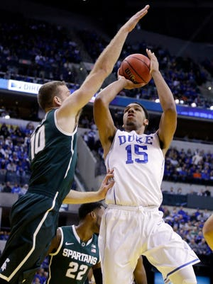 Duke's Jahlil Okafor, right, shoots over Michigan State's Matt Costello in the first half of an NCAA college basketball game in Indianapolis, Tuesday, Nov. 18, 2014. (AP Photo/Michael Conroy)