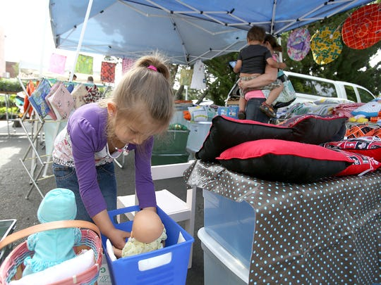 Abby Mack, 5, looks at dolls on Saturday at The Original Independence Farmers Market. The market has been operating for 23 years.