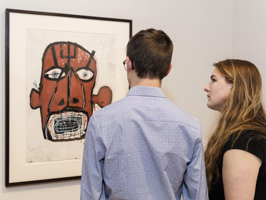 """On display at the Fleming Museum is """"Untitled (Head),"""" a piece by Jean-Michel Basquiat from the collection of Jon Kilik, a 1978 University of Vermont graduate."""